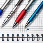 Długopisy reklamowe leżące na otwartym notatniku - Fotografia produktowa aranżowana